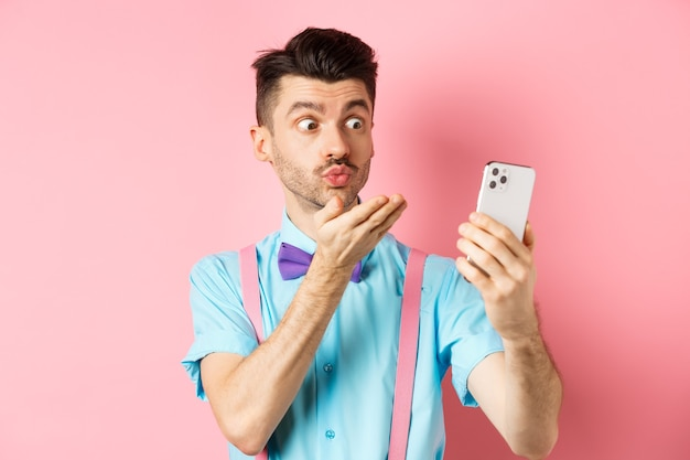 Conceito de tecnologia. homem engraçado mandando beijo no chat por vídeo, soprando mwah para a câmera do smartphone, de pé no fundo rosa.