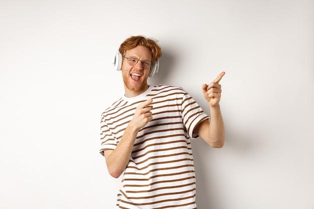 Conceito de tecnologia. homem ruiva feliz ouvindo música em fones de ouvido e dançando e apontando os dedos certos, em pé sobre um fundo branco.