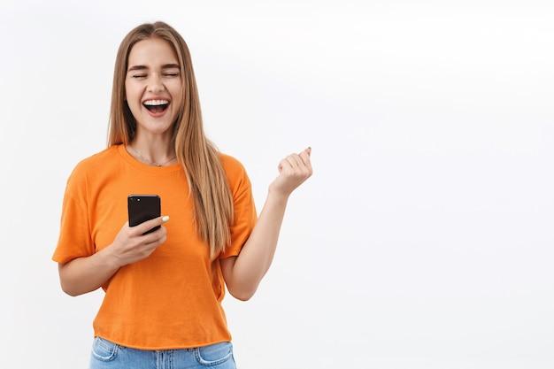Conceito de tecnologia, juventude e comunicação. garota loira sortuda satisfeita vencendo, gritando sim e sorrindo de alegria, cerrar o punho enquanto triunfando, segurando o telefone celular, tenho boas notícias pelo correio