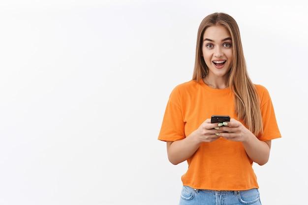 Conceito de tecnologia, juventude e comunicação. retrato de uma linda garota loira usando telefone celular, enviando mensagens de texto para amigos, usando o aplicativo, recomendar o download do aplicativo, fazer upload de novo conteúdo no blog