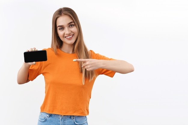 Conceito de tecnologia, juventude e comunicação. retrato de uma linda garota satisfeita, recomendando fazer upload de um novo aplicativo, filtro de fotos, site de compras online apontando o dedo para a tela do celular, sorrindo satisfeito