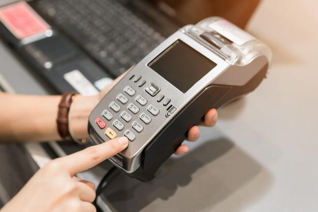 Conceito de tecnologia na compra sem usar dinheiro. feche acima do cartão de crédito do uso da mão.
