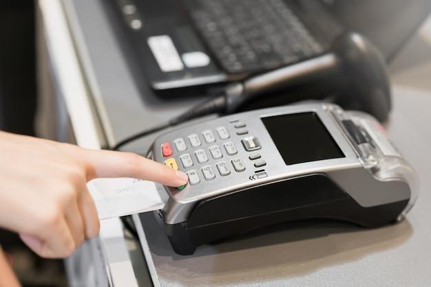 Conceito de tecnologia na compra sem usar dinheiro. mão usar máquina de cartão de crédito swiping para pagar.
