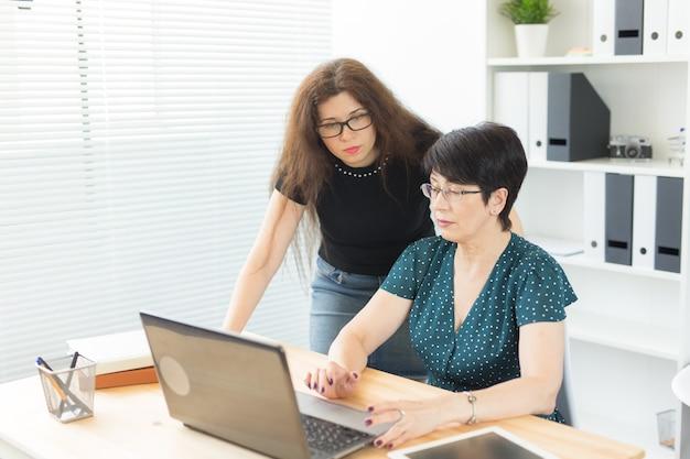 Conceito de tecnologia, negócios e pessoas - jovem mulher explicando algo sobre laptop para sua colega.