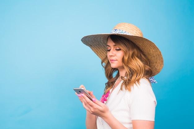 Conceito de tecnologia, pessoas e dispositivos modernos - mulher sorridente, escrevendo no telefone, mensagem de texto vista lateral sobre fundo azul com espaço de cópia.