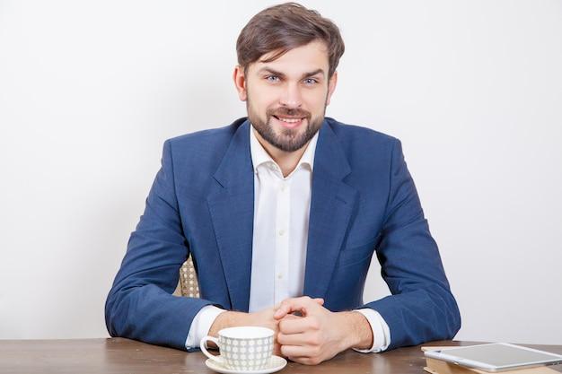 Conceito de tecnologia, pessoas e negócios - homem bonito com barba e cabelo castanho e terno azul e computador tablet pc e alguns livros olhando para a câmera com sorriso ... isolado no fundo branco. .