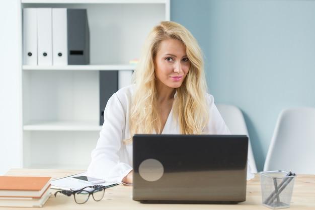 Conceito de tecnologia, trabalho e pessoas - linda mulher loira sentada em sua mesa e trabalhando no laptop.