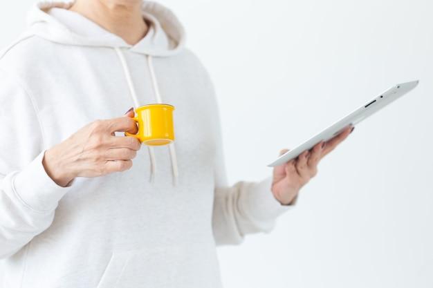 Conceito de tecnologias e pessoas modernas - close-up de mulher segurando o tablet e uma pequena xícara de café amarela na sala iluminada