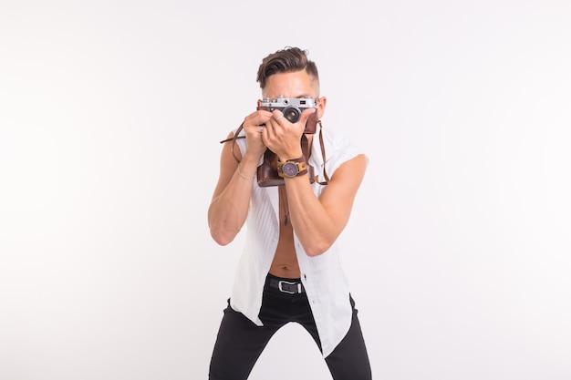 Conceito de tecnologias, fotografia e pessoas - jovem bonito com câmera retro sobre a superfície branca.