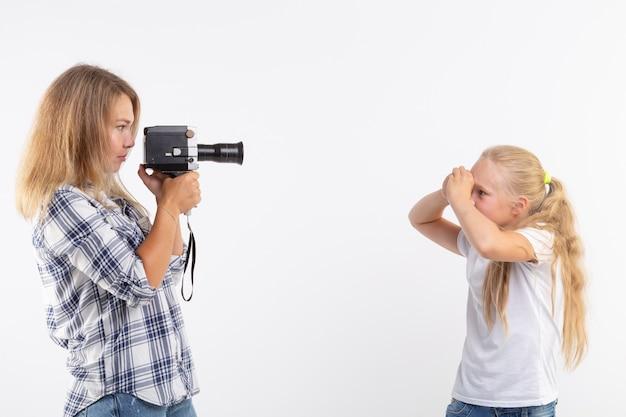 Conceito de tecnologias, fotografia e pessoas - jovem loira com câmera retro fotografando