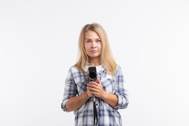 Conceito de tecnologias, fotografia e pessoas - jovem loira com câmera retro sobre branco
