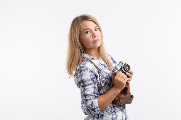 Conceito de tecnologias, fotografia e pessoas - jovem loira com câmera retro sobre uma superfície branca com espaço de cópia
