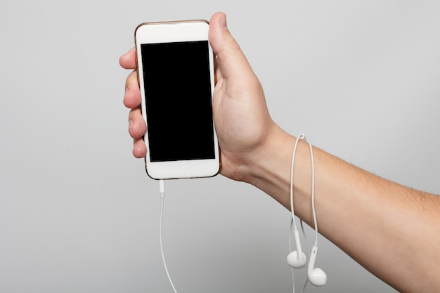 Conceito de tecnologias, pessoas e estilo de vida - mão segure a tela preta do telefone, maquete, novo smartphone, estilo moderno, cor branca fosca