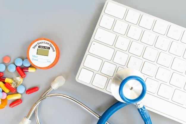 Conceito de telemedicina online, estetoscópio e comprimidos com teclado de pc