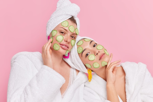 Conceito de tempo de beleza. jovens mulheres sérias e diversas aplicam rodelas de pepino no rosto