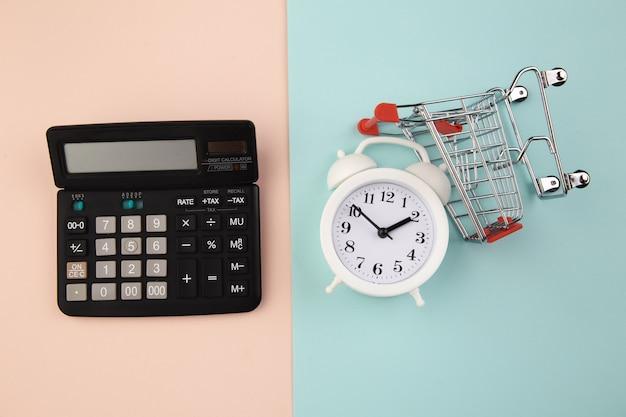 Conceito de tempo de compras. carrinho de supermercado com despertador e calculadora. vista do topo.