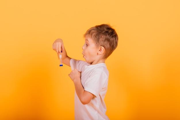 Conceito de tempo de criança - pré-escolar masculino sério gostando de aprender sobre o tempo, segurando uma ampulheta, foto do estúdio