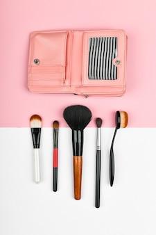 Conceito de tempo de maquiagem. pincéis de maquiagem. cosméticos maquiagem e acessórios para configuração plana. composição com despertador vermelho e cosméticos em uma cor. conceito de maquiagem.