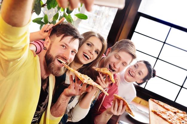 Conceito de tempo de selfie. amigos comem pizza em um café, sorriem e se atiram na câmera do smartphone