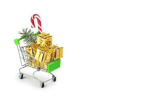 Conceito de temporada de compras de natal mini carrinho de compras caixa cheia de presente isolada no branco