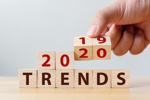 Conceito de tendência 2020. mudança manual do cubo de madeira para o ano de 2019 a 2020