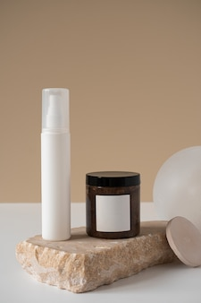 Conceito de terapia de cuidados de beleza estética minimalista. frasco de spray, frasco de creme corporal em branco, pedra de mármore contra bege neutro
