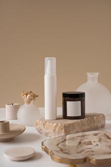 Conceito de terapia de cuidados de beleza estética minimalista. frasco spray, creme, pedra de mármore com flor contra bege neutro