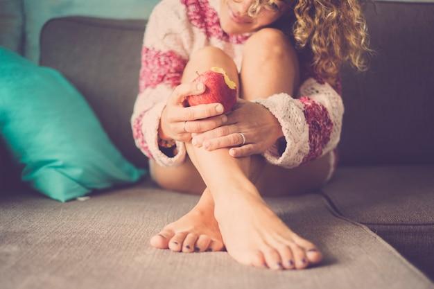 Conceito de ternura com linda mulher de cabelo encaracolado caucasiano sorrindo e comendo uma maçã para cuidar de sua saúde e corpo