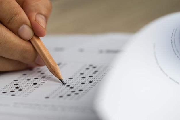 Conceito de teste de educação mãos do aluno segurando uma caneta para os exames escrevendo folha de respostas ou exercício