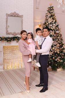 Conceito de tiro de natal, família asiática com dois filhos em roupas elegantes abraçando a árvore
