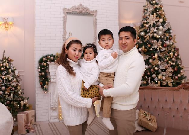 Conceito de tiro de natal, família asiática feliz com dois filhos em suéteres aconchegantes nas árvores