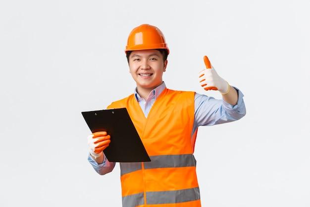 Conceito de trabalhadores industriais e do setor de construção sorrindo satisfeito asiático chefe engenheiro arquiteto maki ...