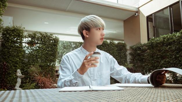 Conceito de trabalho ao ar livre, um garoto legal segurando uma xícara de americano quente trabalhando pacificamente em um espaço de co-working de seu condomínio.