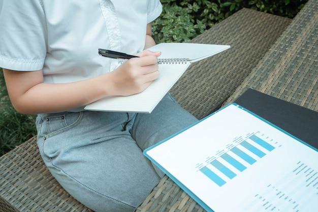 Conceito de trabalho ao ar livre, uma adolescente sentada em um jardim, escrevendo para resumir as informações do gráfico.