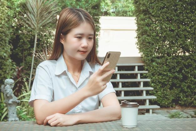 Conceito de trabalho ao ar livre, uma adolescente sentada pacificamente em um jardim com muitas árvores verdes, enquanto usa seu dispositivo na internet.
