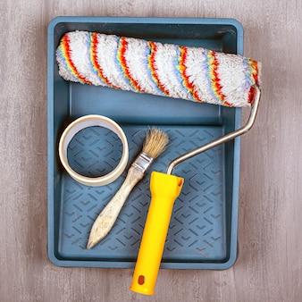 Conceito de trabalho de pintura. conjunto de ferramentas para pintar e reparar paredes. rolo e pincel.