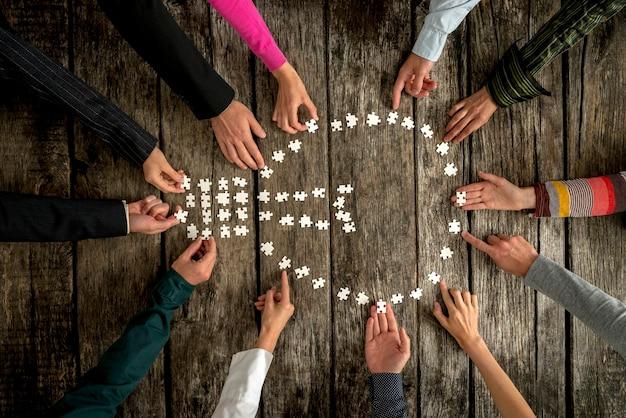 Conceito de trabalho em equipe e cooperação - grupo de doze pessoas, masculinos e femininos, montando uma forma de lâmpada com peças de quebra-cabeça em branco em uma mesa de textura rústica, vista superior.