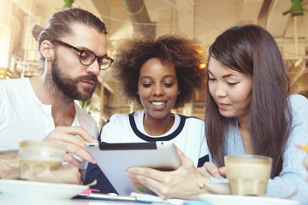 Conceito de trabalho em equipe e cooperação. três jovens talentosos e ambiciosos fazendo um brainstorming, discutindo um projeto comum usando tablet digital no refeitório.