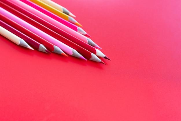 Conceito de trabalho em equipe. grupo de lápis de cor no fundo rosa