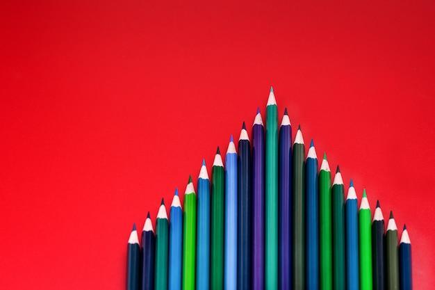 Conceito de trabalho em equipe. grupo de lápis de cor sobre fundo vermelho