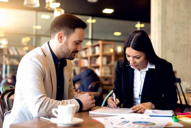 Conceito de trabalho. jovens colegas trabalhando em novos planos, fazendo cálculos trabalhando no escritório moderno.