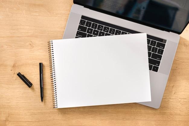 Conceito de trabalho ou educação on-line caderno em branco com laptop na vista superior de mesa de madeira