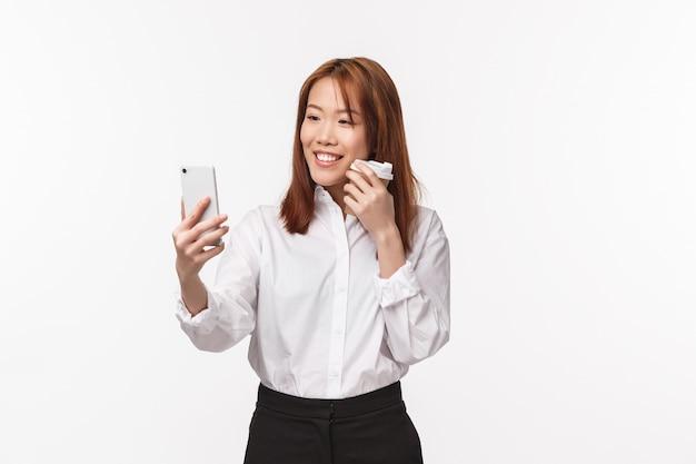 Conceito de trabalho, pessoas e estilo de vida de escritório. retrato de mulher asiática elegante e bonita tomando selfie, gravar vídeo para postar mídias sociais, usando o filtro de aplicativo para foto com café take-away, sorrindo