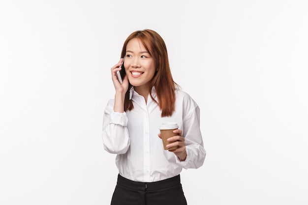 Conceito de trabalho, pessoas e negócios de escritório. retrato de linda garota asiática tomando café e falando no telefone com um sorriso satisfeito e divertido, tendo uma conversa despreocupada enquanto no intervalo na parede branca