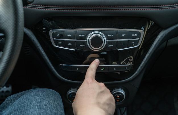 Conceito de transporte e veículo - homem usando o sistema de áudio estéreo do carro