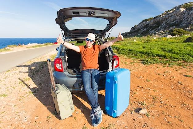 Conceito de transporte, lazer, road trip e pessoas. homem feliz, aproveitando a viagem e as férias de verão.