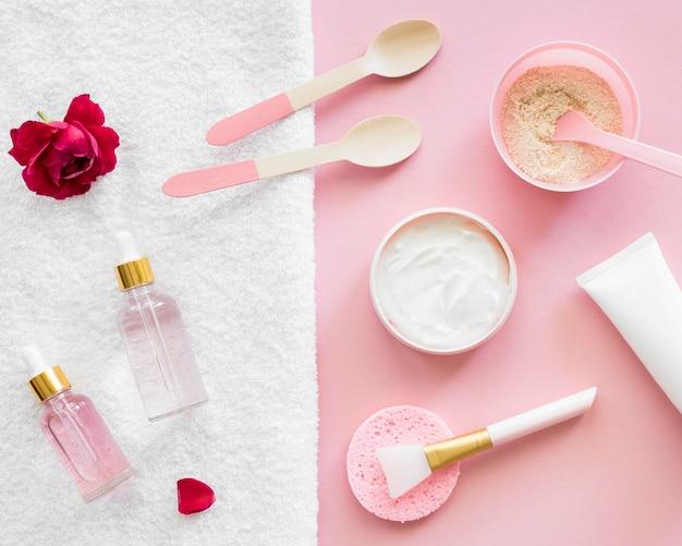 Conceito de tratamento de spa com produtos rosa e escova de maquiagem