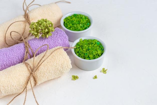 Conceito de tratamento de spa, com sal de banho do mar natural e perfumado de dois tons e toalhas de banho.