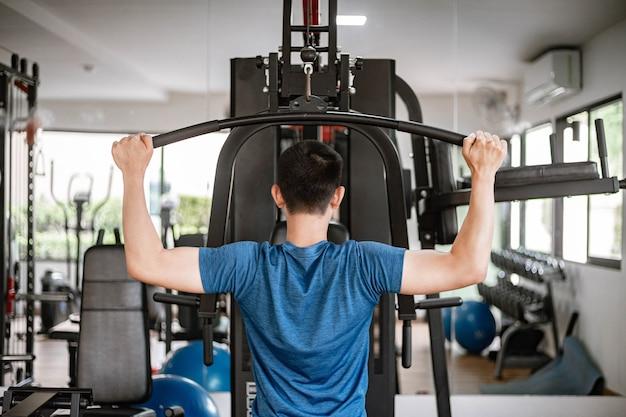 Conceito de treinamento de ginásio, um adolescente do sexo masculino usando um equipamento de ginástica