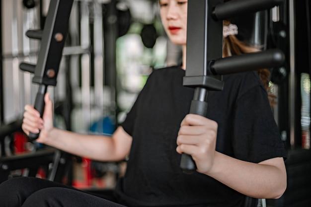Conceito de treinamento de ginásio, uma adolescente do sexo feminino usando um equipamento de ginástica Foto Premium